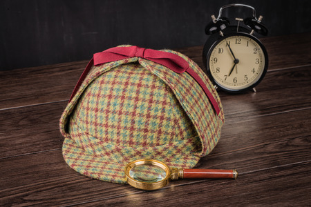animal private: Deerstalker or Sherlock Hat and magnifying glass on Old Wooden table.