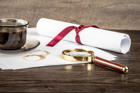 holmes: Coffee cup, paper sheets and detective magnifying glass on old Wooden table. Stock Photo