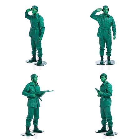 plastic soldier: Four man on a green toy soldier costume standing with riffle isolated on white background.