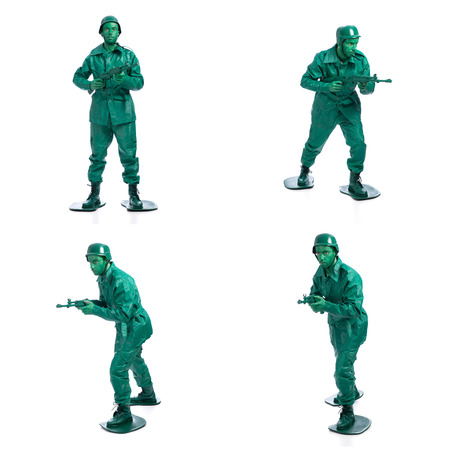 green plastic soldiers: Four man on a green toy soldier costume standing with riffle isolated on white background.