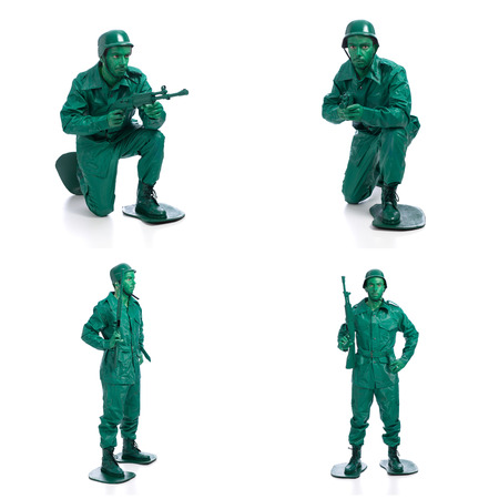 green military miniature: Four man on a green toy soldier costume standing with riffle isolated on white background.