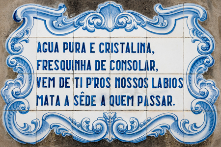 poem: OVAR, PORTUGAL - SEPTEMBER 3, 2015: Panel of traditional Portuguese tiles hand-painted blue and white, with written quoted verses from a poem about water. Editorial