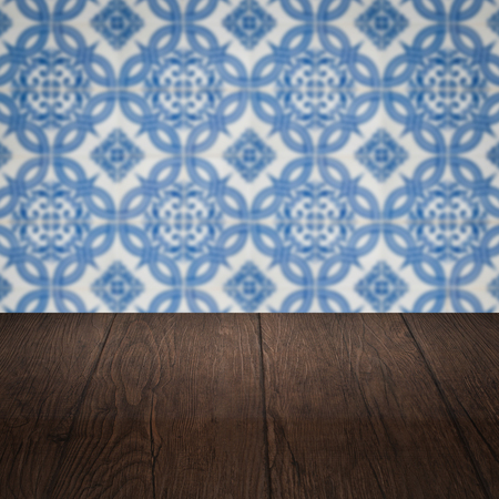 antique table: Empty wood table top and blur vintage ceramic tile pattern wall in background, Mock up template for display of your product.