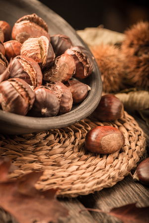 tots: Roasted chestnuts on a rustic wooden table with autumn leaves in the background.
