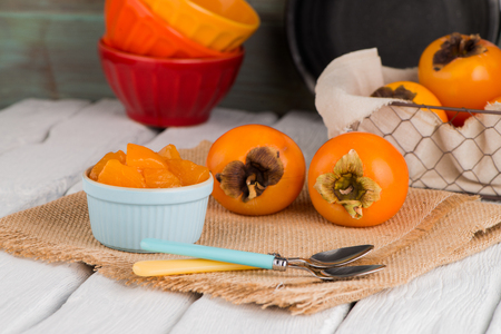 Delicious orange persimmons on wooden table
