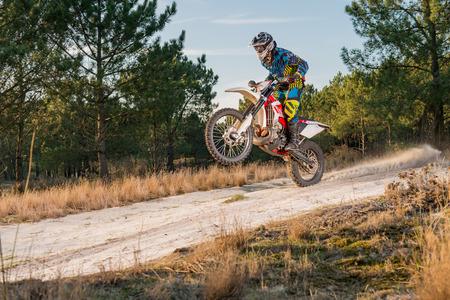 Enduro bike rider on action. Wheelie on sand terrain. Stock Photo