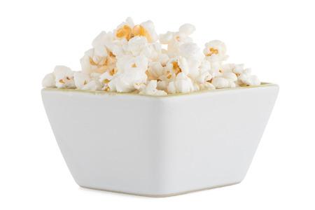 palomitas: Palomitas de maíz en un plato blanco sobre un fondo blanco