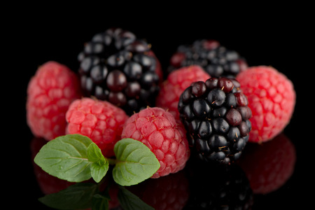 mellow: Composition from a blackberry and raspberry on the black isolated background
