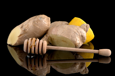 drizzler: Ginger root drizzler with honey and lemon on black reflective background. Concept of natural ingredients to prevent colds. Stock Photo