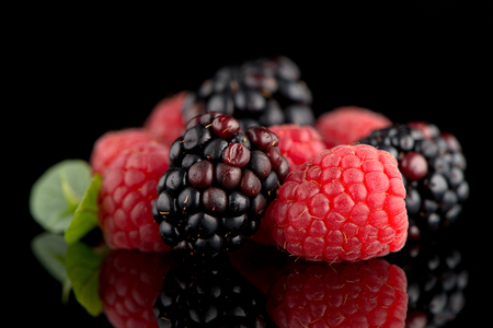 black raspberries: Composition from a blackberry and raspberry on the black isolated background