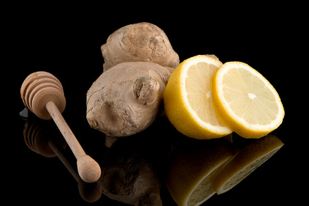 drizzler: Ginger root drizzler with honey and lemon on black reflective background.