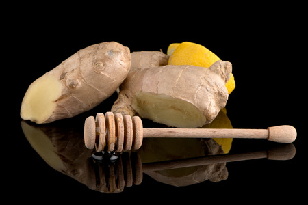 drizzler: Ginger root drizzler with honey and lemon on black reflective background Stock Photo