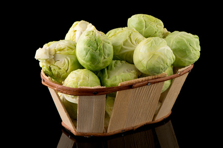 Fresh brussels sprouts and wooden baslet isolated on black background.