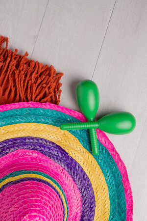 yellow tassel: Mexican sombrero, blanket and pair of maracas on wood background.