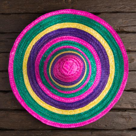 serape: Mexican sombrero on old dark wood background.