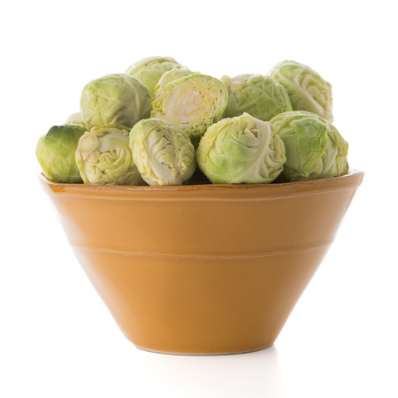 grocer: Fresh brussels sprouts on green ceramic bowl isolated on white background.
