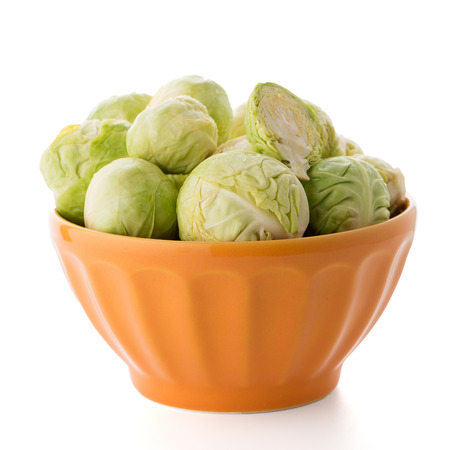 Fresh brussels sprouts on orange ceramic bowl isolated on white background.