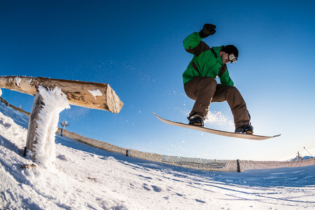 free riding: Snowboarder jumping from a wood rail against blue sky.