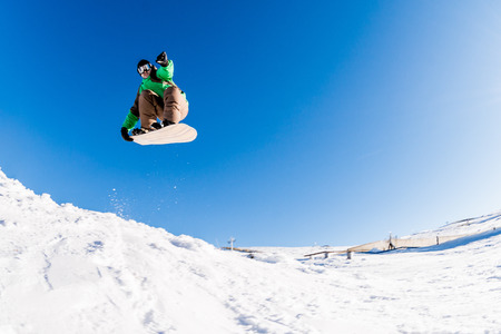 free riding: Snowboarder executing a radical jump against blue sky.