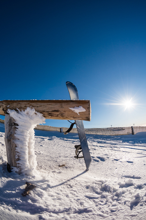non urban scene: Snowboard leaning on a wood rail on a winter snow covered mountainside and sun shine in blue sky. Stock Photo