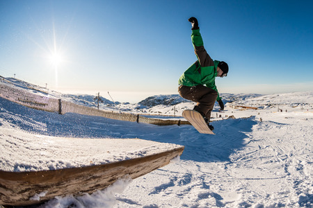 snowboarder jumping: Snowboarder jumping from a wood rail against blue sky.