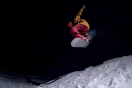 snowboarder: Snowboarder jumping at night.