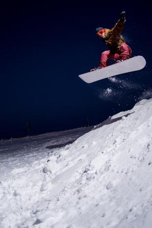 snowboarder jumping: Snowboarder jumping at night.