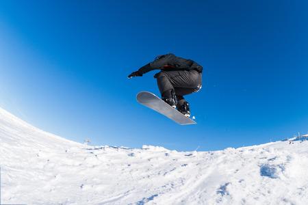 radical: Snowboarder executing a radical jump against blue sky.