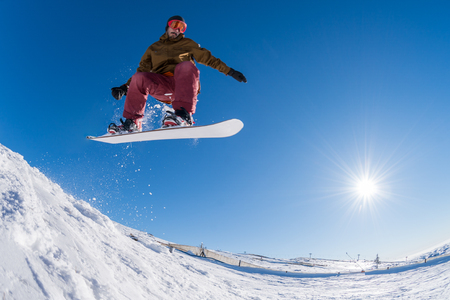 radical: Snowboarder executing a radical jump against blue sky.
