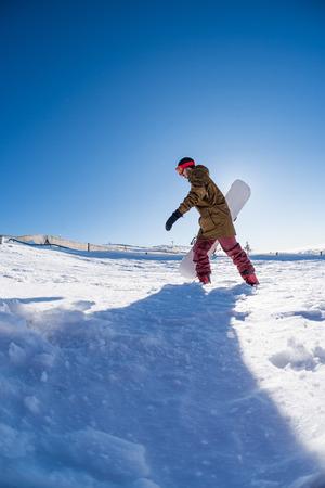 deep powder snow: Snowboarder walking through deep fresh snow against blue sky.