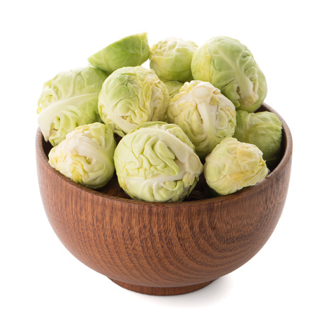 grocer: Fresh brussels sprouts on brown wood bowl isolated on white background.