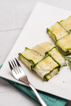 courgettes: Interlaced courgettes or zucchini slices and meat with grated cheese ready to be eaten
