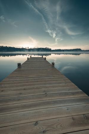 peace plan: Pier leading out onto the lake, sunrise on lake.