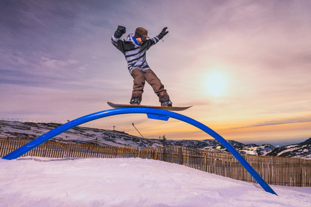 radical: A snowboarder executes a radical slide on a rail in a snow park.