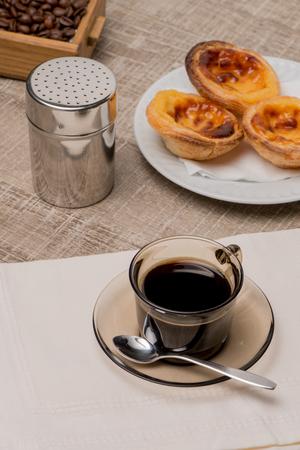 nata: Pasteis de Nata or Portuguese Custard Tarts with black coffee on wooden table.