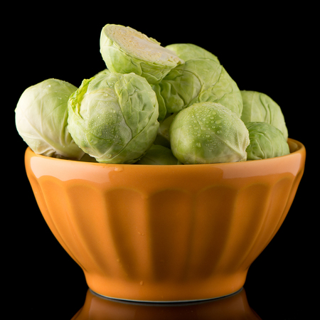 Fresh brussels sprouts on orange ceramic bowl isolated on black background.
