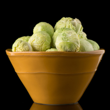 Fresh brussels sprouts on green ceramic bowl isolated on black background.