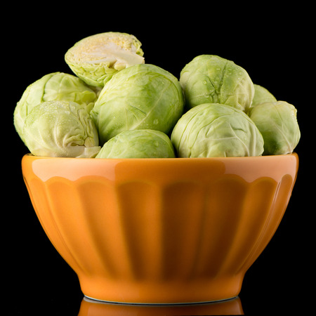 grocer: Fresh brussels sprouts on orange ceramic bowl isolated on white background.