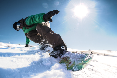 freerider: Snowboard freerider in the mountains against sun shine in blue sky.