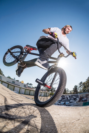 stunt: Bmx stunt performed at the top of a mini ramp on a skatepark.