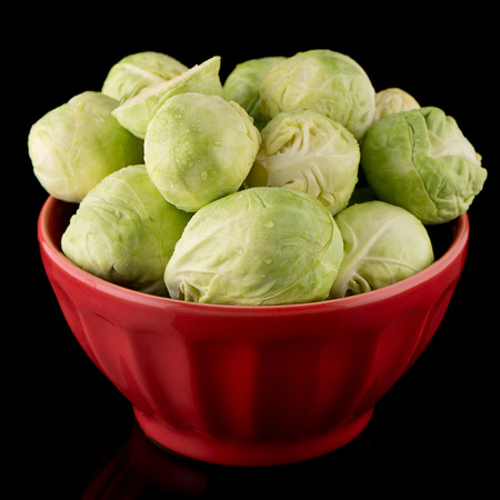 Fresh brussels sprouts on red ceramic bowl isolated on black background. Stock Photo