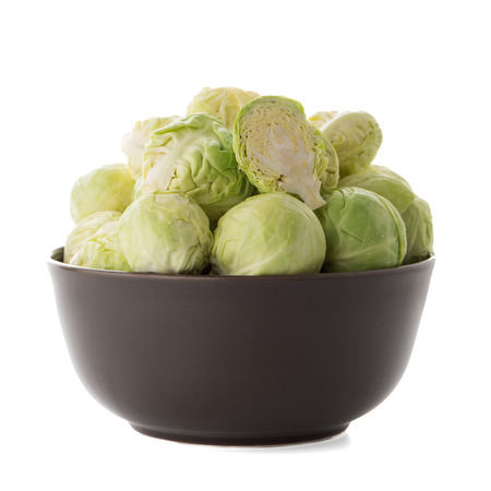 Fresh brussels sprouts on brown ceramic bowl isolated on white background.