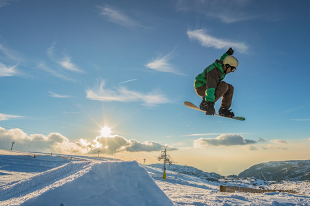 Snowboarder executing a radical jump against sunset sky.