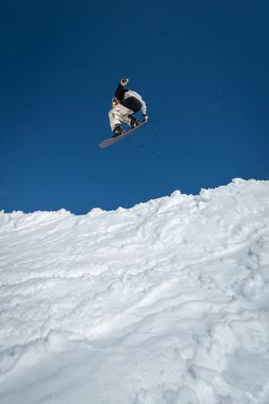 Snowboarder executing a radical jump against blue sky.