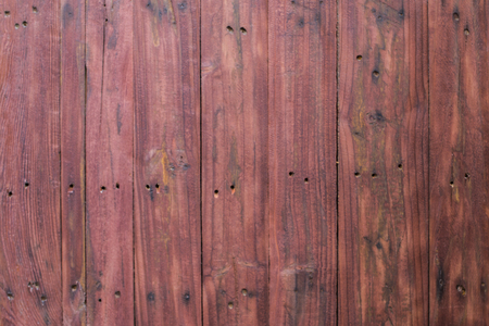 Grungy red paintwork on a wooden panel