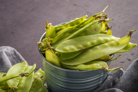 snap bean: Organic Green Sugar Snap Peas Ready to Eat on cement background.