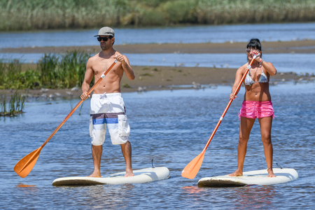 Man and woman stand up paddleboarding on lake. Young couple are doing watersport on lake. Male and female tourists are in swimwear during summer vacation. Stock Photo