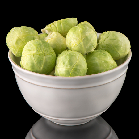 Fresh brussels sprouts on white ceramic bowl isolated on black background.