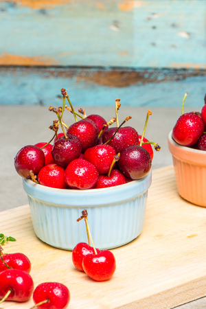 countertop: Red ripe cherries in ceramic bowls on kitchen countertop.
