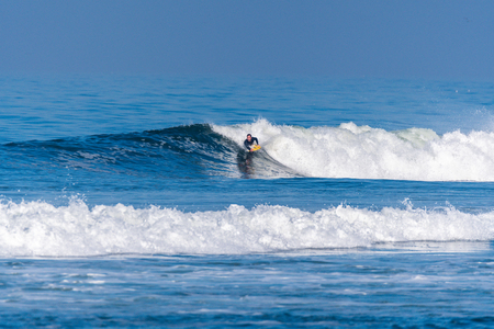 Bodyboarder in action on the ocean waves on a sunny day. Stock Photo